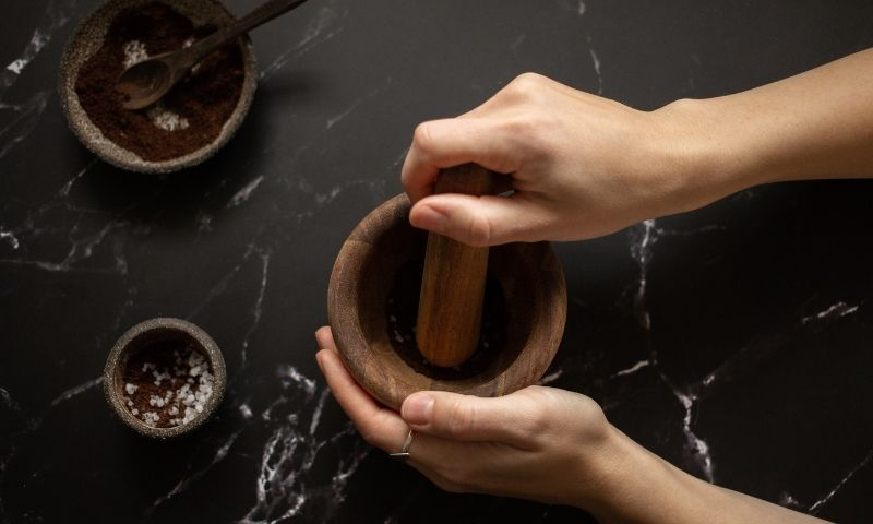 manos usando un mortero para tratar con productos naturales
