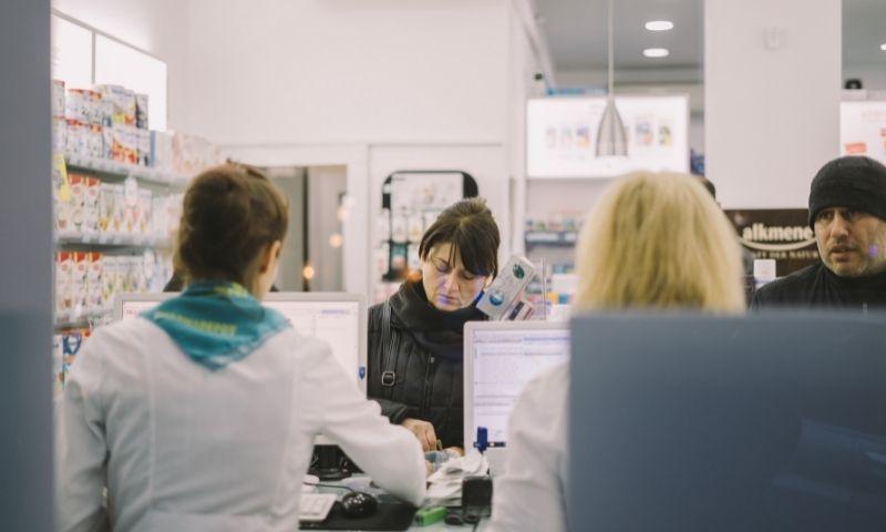 farmacéuticas atendiendo a clientes en una farmacia