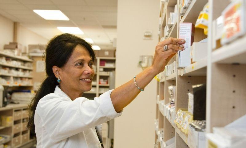 Farmacéutica titular colocando medicamentos en una estantería